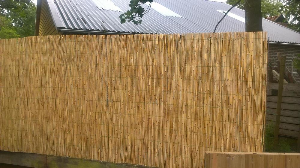 Rietmatten boven een bestaande houten schutting